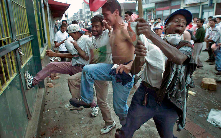 1/29/99 Al Diaz/Herald staff--In downtown Armenia  looters in search of food try to kick a store front door. Tens of thousands of Colombians are left homeless after Monday's devastating earthquake.
