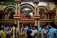 INDIA (West Bengal - Calcutta)  2008, A Durga pandal in Kolkata. Common Indian people visiting pandal/altar during the days of Durga Puja Festival.  Durga Puja Festival is the biggest festival among bengalies.  As Calcutta is the capital of West Bengal and cultural hub of  the bengali community Durga puja is held with the maximum pomp and vigour. Ritualistic worship, food, drink, new clothes, visiting friends and relatives places and merryment is a part of it. In this festival the hindus worship a ten handed godess riding on a lion armed wth all possible deadly ancient weapons along with her 4 children (Ganesha - God for sucess, Saraswati - Goddess for arts and education, Laxmi - Goddess of wealth and prosperity, Kartikeya - The god of manly hood and beauty). Durga is symbolised as the women power in Indian Mythology.  In Calcutta people from all the religions enjoy these four days of festival in the moth of October. Now the religious festival has become the biggest cultural extravagenza of Calcutta the cultural capital of India. Artistry and craftsmanship can be seen in different sizes and shapes in form of the idol, the interior decor and as well as the pandals erected on the streets, roads and  parks.- Arindam Mukherjee