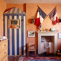 A wardrobe masquerading as a Punch and Judy tent makes good use of an alcove next to the old-fashioned stone fireplace in this child's bedroom