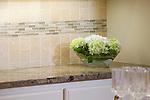 Detail shot of neutral-colored tile backsplash and granite countertop