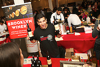 New York, NY - October 30, 2014: A server from Brooklyn Winery presents wine options to guests at Edible Escape, hosted by Edible Manhattan magazine, at the Metropolitan Pavillion in Chelsea. <br /> <br /> CREDIT: Clay Williams for Edible Manhattan<br /> <br /> &copy; Clay Williams / claywilliamsphoto.com