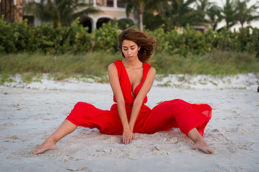 Elegant beautiful barefoot young woman sitting on a beach in the sand wearing a stylish red outfit