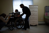 Kelly Kacinski (left, sister) and Maureen Kacinski (mother) adjust the wheelchair for Teresa Kacinski, 46, (right) in Teresa's bedroom in one of the residences in Malone Park at the Fernald Developmental Center in Waltham, Massachusetts, USA.  Teresa is confined to a wheelchair, cannot speak, and needs to have her hands restrained when she is awake. Teresa is the youngest resident at the center.