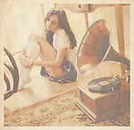 A young woman sitting on the floor listening to an old gramaphone record.