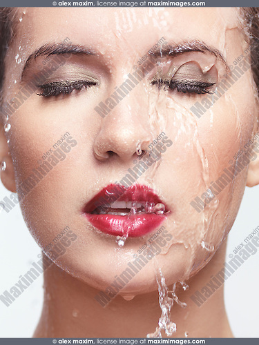 Closeup of a young beautiful woman face with red lipstick and makeup with water running over it