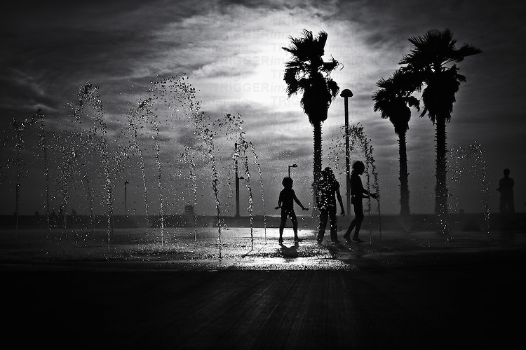 Conceptual beach scene with young children playing in water fountain