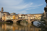 General view of Ponte Vecchio, Florence, Tuscany, Italy, pictured on June 10, 2007, in the afternoon. The Ponte Vecchio, or Old Bridge, crosses the River Arno at its narrowest point. The original bridge, possibly Roman and first documented in 999, was swept away in a flood in 1117, rebuilt, swept away again in 1333 and rebuilt in 1345. In 1565 Cosimo de Medici commissioned Vasari to design a corridor, above the famous shops along the bridge, connecting the Palazzo Vecchio to the Pitti Palace. In 1593 the Medicis prohibited butchers, the traditional occupants, from the shops which were soon taken by Goldsmiths. Florence, capital of Tuscany, is world famous for its Renaissance art and architecture. Its historical centre was declared a UNESCO World Heritage Site in 1982. Picture by Manuel Cohen.
