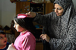 Souad Kasem Issa combs the hair of her daughter Rahaf, 9, while her son Nour Eddin, 5, looks on. She is a Syrian refugee in Amman, Jordan. She and her husband and six children fled the city of Homs as fighting there worsened in 2012. Their home in Syria has since been destroyed by bombing, and they are struggling to survive in Jordan's capital city, where they have received help from International Orthodox Christian Charities, a member of the ACT Alliance.