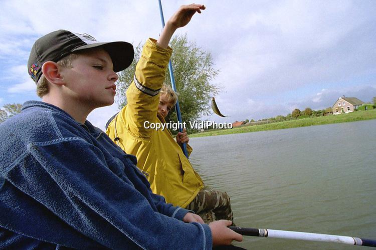 Foto: VidiPhoto..DOORNENBURG - De meeste vis zit op de plek waar de Linge begint, vlak voor kasteel Doornenburg. Althans dat beweren deze sportvissertjes. Hun herfstvakantie wordt gebruikt om lekker te hengelen. Het ene na het andere voorntje wordt omhoog getakeld, om vervolgens te dienen als levend aas voor een flinke snoek. Het gebruik van het levende aasvisje is sinds vorig jaar verboden, maar daar trekken de jongens zich weinig van aan.