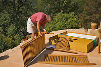 Man assembles flat packed garden furniture on the terrace of his house.Model Released.