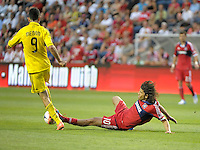 Chicago midfielder Sebastian Grazzini (10) attempts to slide tackle the ball away from Columbus midfielder Justin Meram (9).  The Chicago Fire defeated the Columbus Crew 2-1 at Toyota Park in Bridgeview, IL on June 23, 2012.