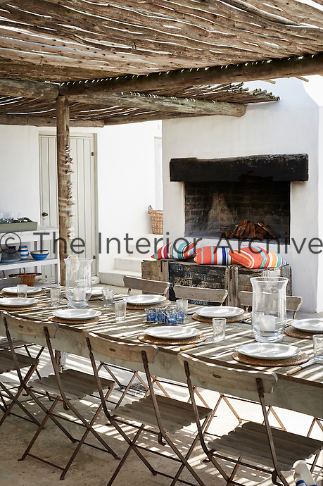 A wooden table and chairs are set out on a covered terrace with an outdoor fireplace. The table is set for lunch with white tableware.