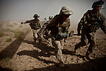 "10/8/2010 Marjah, Helmand Province, Afghanistan.US Marines carry a wounded comrade on a stretcher towards the landing zone after their MAT-V MRAP vehicle was hit by a roadside bomb, wounding 4, in Marjah, Helmand Province...The Helicopter Medevac teams of Task Force Destiny, based at Forward Operating Base Dwyer in Afghanistan's war-torn Helmand Province have a tough job. Servicing a large area that includes still restive southern Marjah, and much of the Helmand River Valley, TF Destiny answers the call to transport gravely wounded US Marines and Afghan civilians from the point of injury in the field to Role 3 trauma centers on bases in the area--often times landing under fire to extract Marines and soldiers that would otherwise succumb to their wounds. After the Medevac helicopter and it's ""chase"" UH-60 Blackhawk companion aircraft get a call, they can be on the ground picking up a patient in as little as 20 minutes--delivering the fallen to a surgical theater within what flight medics refer to as ""the golden hour""--or the hour after a catastrophic injury during which a patients transfer from basic battlefield triage care to a modern trauma surgical unit can mean the difference between life and death. ."