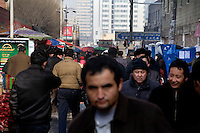 Uighurs walk along the streets of the Uighur section of Urumqi, Xinjiang, China.  The city is divided between Han and Uighur ethnic groups and in 2009 saw violent clashes between the groups.