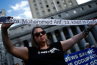 New York, USA. 24 July 2014. A woman holds the name of a person killed in gaza during a protest by Palestine supporters in New York, demanding the end of the war by Israel and Hamas in Gaza. Photo by Eduardo Munoz Alvarez/VIEWpress