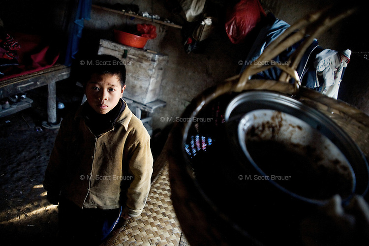 Fan Lu Yang, 10, stands in his grandparents' home in Fanzhuang Village, Gangyun County, Jiangsu, China.  Fan Lu Yang lives with grandfather Fan Qing Huai and grandmother Wang Bao Ying.  The grandparents are both over 75 and often ill, and the income from growing corn, wheat, and hay, cannot support the three.  Fan Lu Yang's father died in 2000 in an accident at a small coal mine and his mother developed dementia and disappeared about a year before this picture was taken...At the time of the picture, China's Amity Foundation charity, was investigating the family's situation in preparation to raise money to financially support these children and other orphans in similar situations.  With Amity's support, each orphan, aged 6-12, would receive approximately 1,400 RMB annually (about 200 USD) to pay for the cost of living. Amity works to keep children out of the institutional orphanages in China, preferring to provide monetary assistance that can help maintain a family environment for the orphans it helps.
