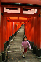 Little Japanese girl running through the Red Torii gates at Fushimi Inari Shrine in Kyoto; Fushimi Inari Shrine is one of Kyoto's landmarks and has been featured in countless movies as backdrop.  A torii is a traditional Japanese gate commonly found at the entry to a Shinto shrine.  The basic structure of a torii is two columns that are topped with a horizontal rail. Slightly below the top rail is a second horizontal rail. Torii are traditionally made from wood and are usually painted vermilion red.