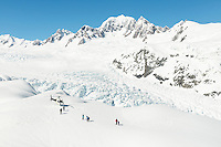 Vast upper parts of Fox Glacier with Mount Tasman and group of people and helicopter in foreground, Westland Tai Poutini National Park, West Coast, UNESCO World Heritage Area, New Zealand, NZ