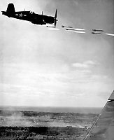 Corsair fighter looses its load of rocket projectiles on a run against a Jap stronghold on Okinawa.  In the lower background is the smoke of battle as Marine units move in to follow up with a Sunday punch.  Ca.  June 1945.  Lt. David D. Duncan.  (Marine Corps)<br /> Exact Date Shot Unknown<br /> NARA FILE #:  127-GR-97-126420<br /> WAR &amp; CONFLICT BOOK #:  1224