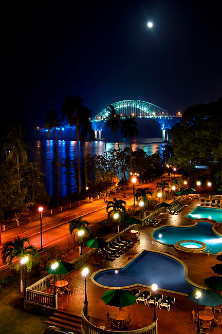 The night moon rises over the Bridge Of The Americas, the Pacific entrance to the Panama Canal.  The last portion of the Amador Causeway runs along Panama Bay<br /> and the pools of a local hotel.