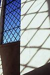 Shadow of diamond-leaded window on white painted wall next to another diamond leaded window showing blue sky
