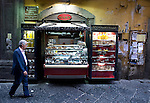 A man passes a pastry shop in the Spaccanapoli shopping district of Naples.