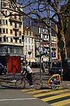 Man on bike pulling baby carriage. Neuchatel, Switzerland.