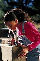 HISPANIC GIRL AT WATER FOUNTAIN. HISPANIC GIRL. SAN FRANCISCO CALIFORNIA USA.