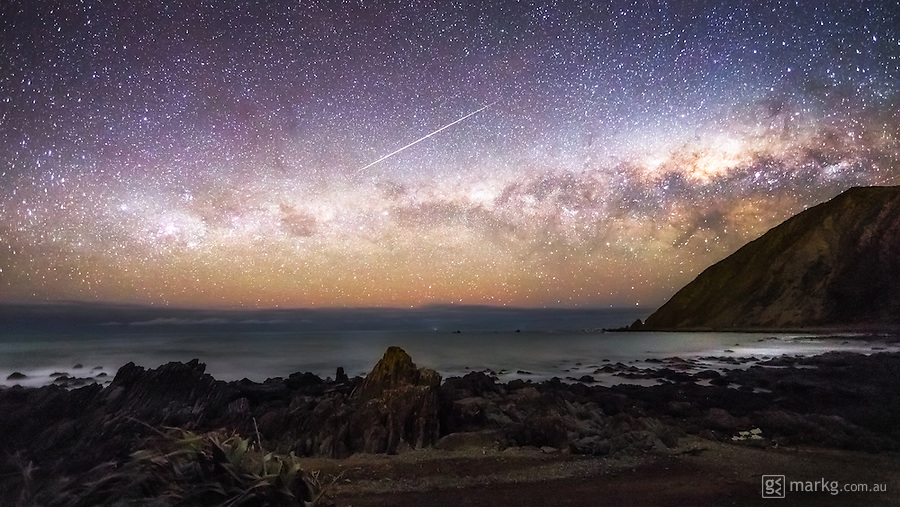 I headed out to the Wellington South Coast in New Zealand to attempt to capture some of the recent aurora activity. The aurora wasn't visible to the naked eye, and the camera was only capturing a faint glow on the horizon, but I proceeded to set up a time-lapse. Within minutes, a huge meteor streaked across the sky burning up in the Earth's atmosphere, and fortunately for me, it was captured in one of the frames of my time-lapse. That certainly made up for the lack of aurora that night!