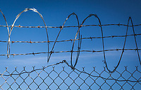 Concertina wire, barbed wire, chain link - keep out.