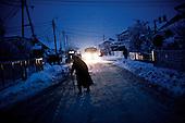 Kotowice 01.2010 Poland<br /> Kotowice were among the first places where blackouts - 12 days ago. People in the evening return home from the neighbors, which went to warm because they could not afford to power generator. In the evenings, the only source of light are the headlights of passing cars.<br /> Three atmospheric forces: rain, snow and frost have changed into an ecological disaster the Myszkowski district in the Czestochowskie province, located 230 kilometers south of Warsaw. Almost 95% of all trees are down.Thousands of homes are left without electricity.<br /> Photo: Adam Lach / Napo Images for Newsweek Polska<br /> <br /> Kotowice byly jednym z pierwszych miejsc gdzie zabraklo pradu - 12 dni temu. Ludzie wieczorami wracaja do domu od sasiadow, do ktorych poszli sie ogrzac albowiem nie bylo ich stac na agregat pradotworczy. Wieczorami jedynym zrodlem swiatla sa reflektory przejezdzajacych samochodow.<br /> Wstepnie &quot;tylko&quot; 95% scietych drzew w dwoch powiatach. 0.5 miliona metrow szesciennych zniszczonych lasow..Tysiace gospodarstw bez pradu. Wszyscy maja swiadomosc, ze na kumulacje trzech niekorzystnych .zjawisk atmosferycznych rady nie ma.Trzy zjawiska kt&oacute;re zamienily jeden z obszarow Polski w istna katastrofe ekologiczna: deszcz, snieg i szadz.<br /> Fot: Adam Lach / Napo Images dla Newsweek Polska