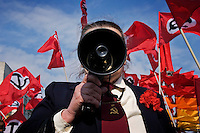 Moscow, Russia, 01/05/2005..Demonstrators from a wide range of political groups take to the streets on the traditional Russian Mayday holiday to protest against President Vladimir Putin and the Russian government..A Communist organiser addresses demonstrators with the flags of the National Bolshevik Party behind.