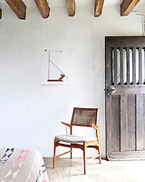 A retro chair is juxtaposed with the open rustic door to one of the cottage bedrooms