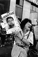 A woman holds up a picture of a 'disapeared' political prisoner during a rally.