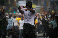 """A masked supporter of the """"Bersih"""" electoral reform coalition holds a national flag against police water cannon during clashes in downtown Kuala Lumpur July 9, 2011. Malaysian police fired tear gas and detained more than 500 people in the capital on Saturday in a bid to prevent thousands of anti-government protesters from putting on a massive show of strength against Prime Minister Najib Razak.  REUTERS/Damir Sagolj (MALAYSIA)"""
