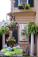 "Small patio garden with house, shade, garden furniture, pot containers, ornaments, hydrangea ""ice cream"", windowboxes, columns with ferns, adorable relics and flea market finds."