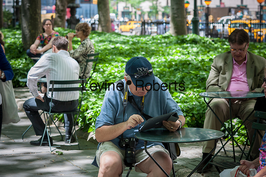A visitor to Bryant Park in New York uses his iPad on Tuesday, June 4, 2013.  (© Richard B. Levine)