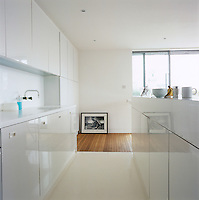 The kitchen area has a white resin floor and gloss Formica cupboard doors and the free-standing kitchen unit has a pull-out table top with seating for up to 6 people