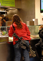 A woman with a gun orders a falafel in downtown Jerusalem.