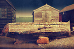 An old fishing boat with for sale sign on keyside with sheds at Walberswick in Suffolk, England.