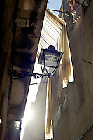 the sun shines through the alley of typical old barcelona, lanterns and shades