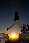 Woman jumping between two boulders at sunset, Coronado National Forest, Arizona