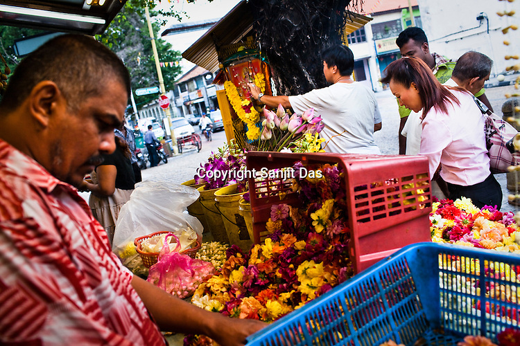Devout Hindu and Chinese devotees buy flowers for worship outside a small Hindu temple in the UNESCO heritage city of Georgetown in Penang, Malaysia. Photo: Sanjit Das/Panos