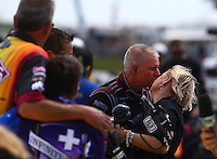 May 22, 2016; Topeka, KS, USA; NHRA funny car driver Tim Wilkerson reacts as he is kissed by wife Krista Wilkerson after crashing during the Kansas Nationals at Heartland Park Topeka. Wilkerson was uninjured in the accident. Mandatory Credit: Mark J. Rebilas-USA TODAY Sports