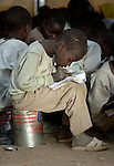 A boy studies in a makeshift classroom in a camp for families displaced by the violence in Sudan's Darfur region.