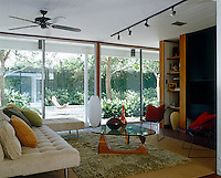 In the living room an entire wall is constructed of glass with a series of sliding glass doors giving instant access to the lush courtyard garden beyond