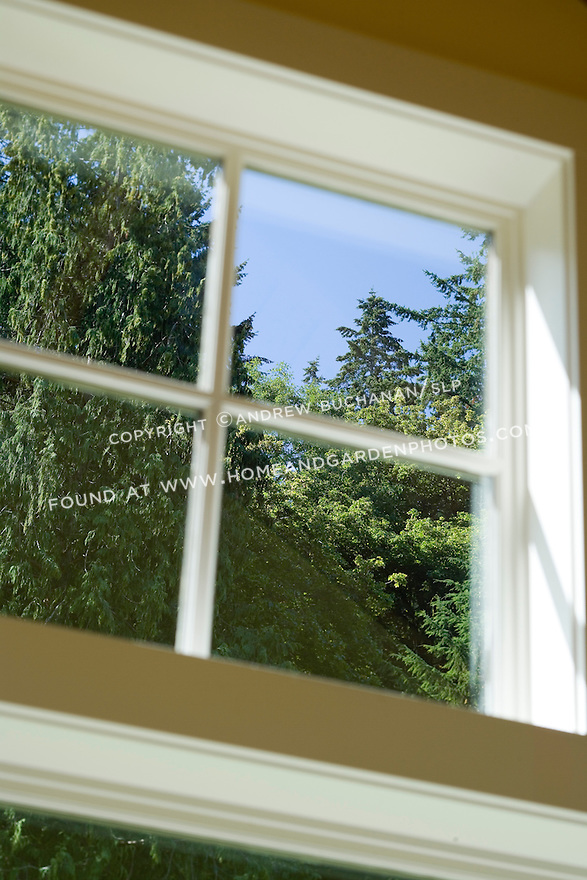 Close-up detail of the view to the tall evergreen trees through a white-painted, mullioned window in soft foreground focus in this waterfront weekend vacation retreat on Washington State's Vashon Island.