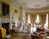 The windows on the curved end of this traditional drawing room are dressed in heavy curtains complementing the delicate cornice and ceiling roses