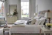 The master bedroom is a haven of tranquility in tones of soft grey and white and the headboard is decorated with a string of battery-powered fairylights