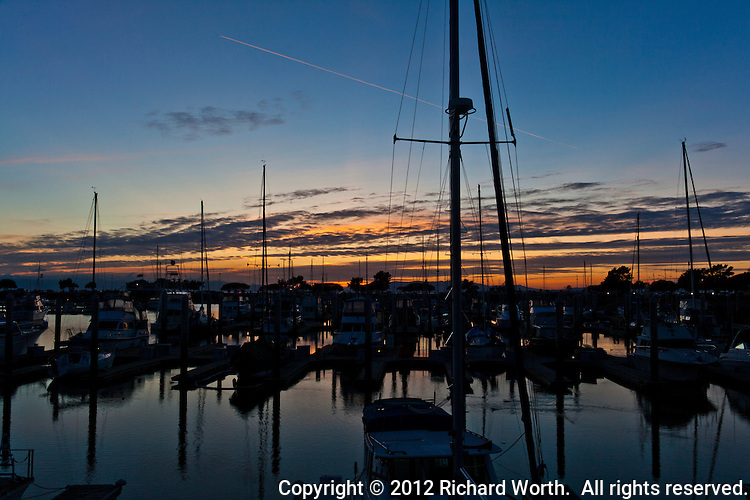Sail boats are moored at the San Leandro Marina at sunset, orange and gold clouds in the distance and a contrail slicing through the darkening sky.
